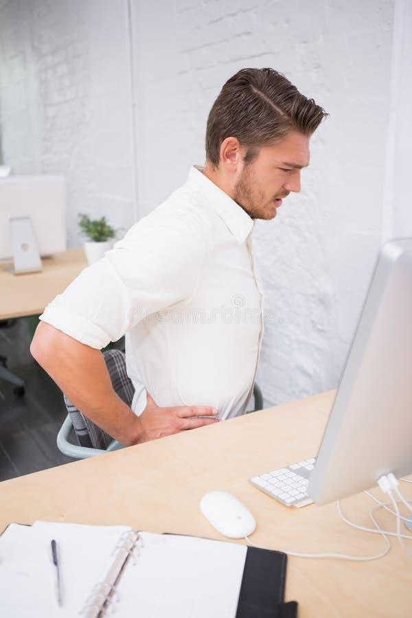 Επιχειρηματίας που πάσχει από τον πόνο στην πλάτη στην αρχή στοκ εικόνα με δικαίωμα ελεύθερης χρήσης