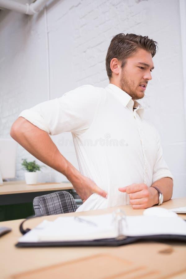 Επιχειρηματίας που πάσχει από τον πόνο στην πλάτη στο γραφείο γραφείων στοκ εικόνες