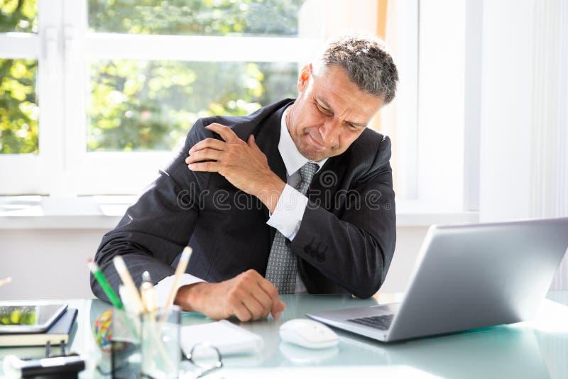 Επιχειρηματίας που πάσχει από τον πόνο ώμων στοκ εικόνες