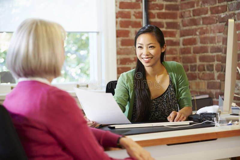 Επιχειρηματίας που παίρνει συνέντευξη από τον υποψήφιο εργασίας θηλυκών στην αρχή στοκ φωτογραφία