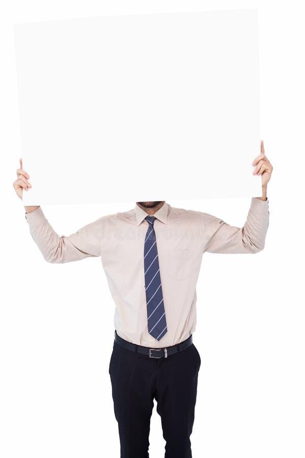 Επιχειρηματίας που παρουσιάζει άσπρη αφίσα μπροστά από το κεφάλι του στοκ εικόνες με δικαίωμα ελεύθερης χρήσης