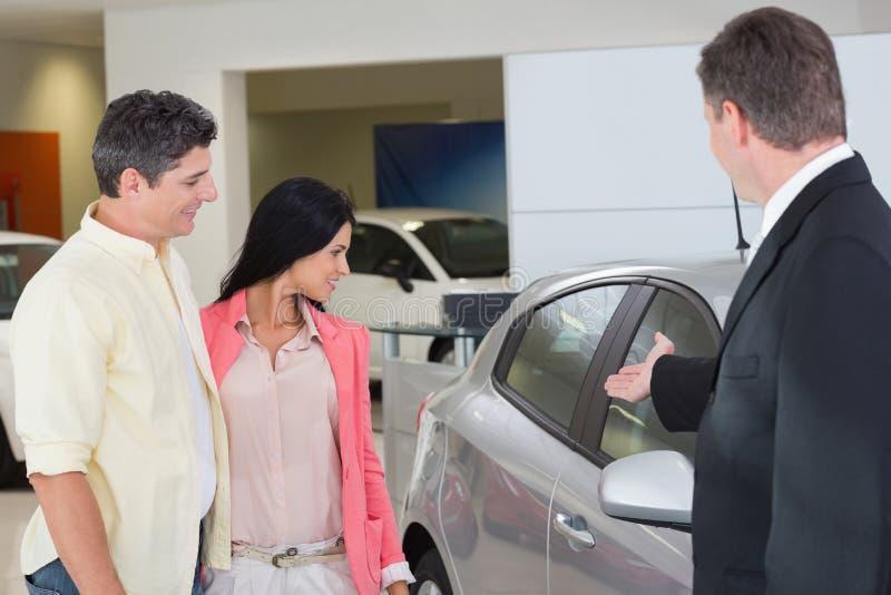 Επιχειρηματίας που παρουσιάζει ένα αυτοκίνητο σε ένα ζεύγος στοκ φωτογραφία με δικαίωμα ελεύθερης χρήσης