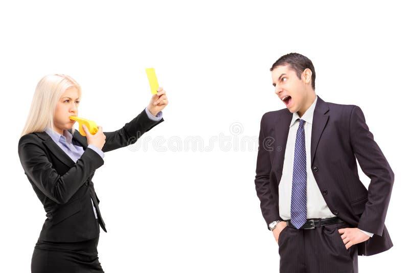 επιχειρηματίας που παρουσιάζει κίτρινη κάρτα σε μια κραυγήη επιχειρηματιών στοκ εικόνα