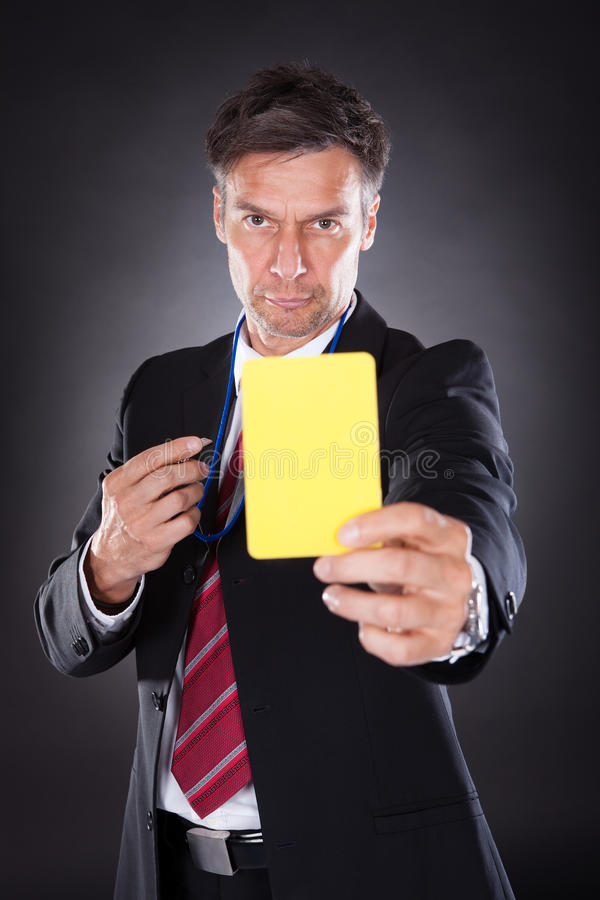 Επιχειρηματίας που παρουσιάζει κίτρινη κάρτα στοκ φωτογραφία με δικαίωμα ελεύθερης χρήσης