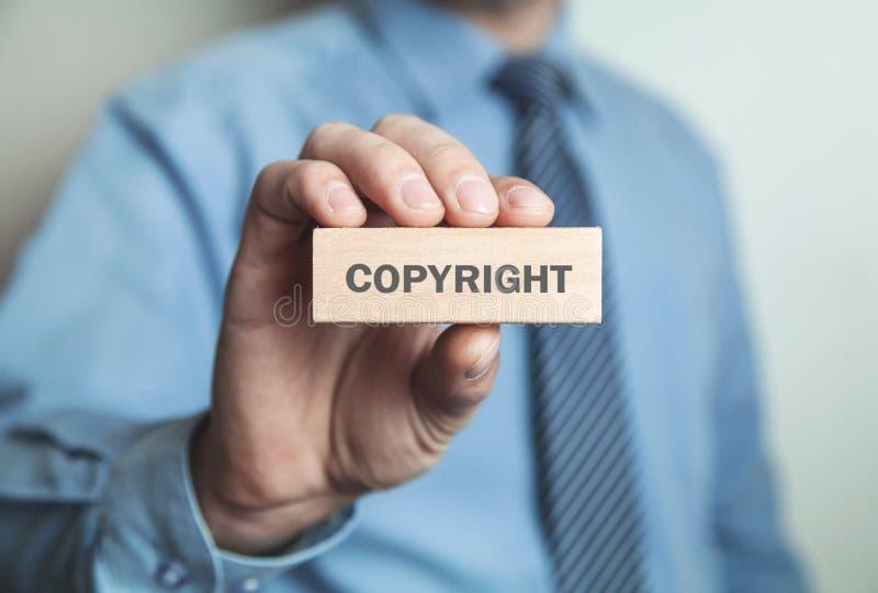 Επιχειρηματίας που παρουσιάζει λέξη πνευματικών δικαιωμάτων στον ξύλινο φραγμό Επιχείρηση con στοκ φωτογραφίες