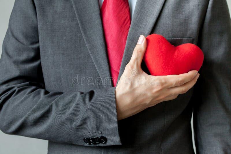 Επιχειρηματίας που παρουσιάζει οίκτο που κρατά την κόκκινη καρδιά επάνω στο στήθος του στοκ εικόνες
