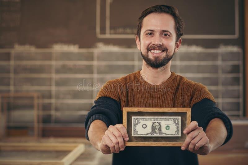 Επιχειρηματίας που παρουσιάζει πλαισιωμένο τραπεζογραμμάτιο με ένα υπερήφανο χαμόγελο στοκ εικόνες με δικαίωμα ελεύθερης χρήσης