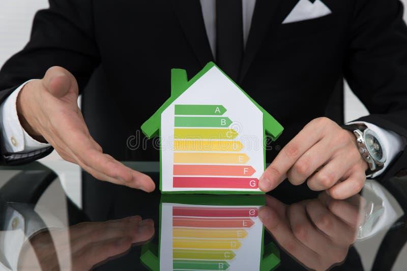 Επιχειρηματίας που παρουσιάζει στην ενέργεια αποδοτικό διάγραμμα στο πρότυπο σπιτιών στοκ εικόνα