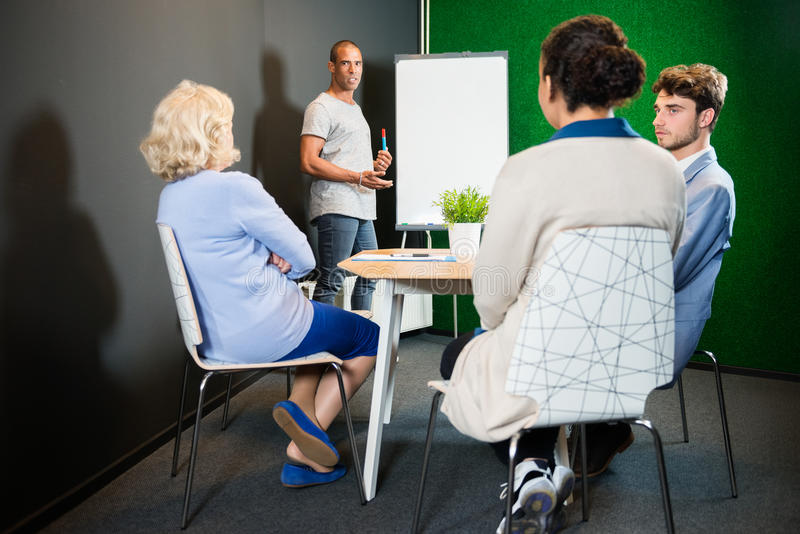 Επιχειρηματίας που παρουσιάζει στους συναδέλφους στην αρχή στοκ φωτογραφίες