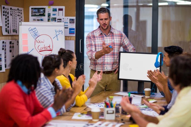 Επιχειρηματίας που παρουσιάζει στους συναδέλφους στην αρχή στοκ εικόνα