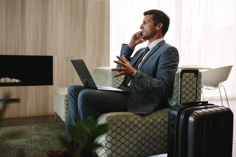 Επιχειρηματίας που περιμένει την πτήση του στο σαλόνι αερολιμένων στοκ φωτογραφία