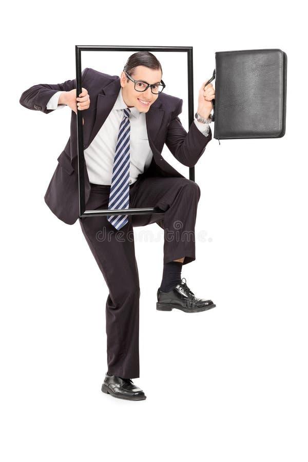Επιχειρηματίας που περπατά μέσω ενός πλαισίου στοκ φωτογραφία με δικαίωμα ελεύθερης χρήσης