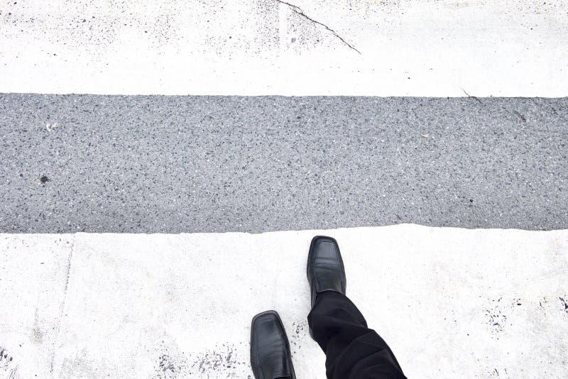 Επιχειρηματίας που περπατά πέρα από τη διάβαση πεζών Μαύρα παπούτσια δέρματος και μαύρη βραδύτητα Τοπ όψη στοκ φωτογραφίες