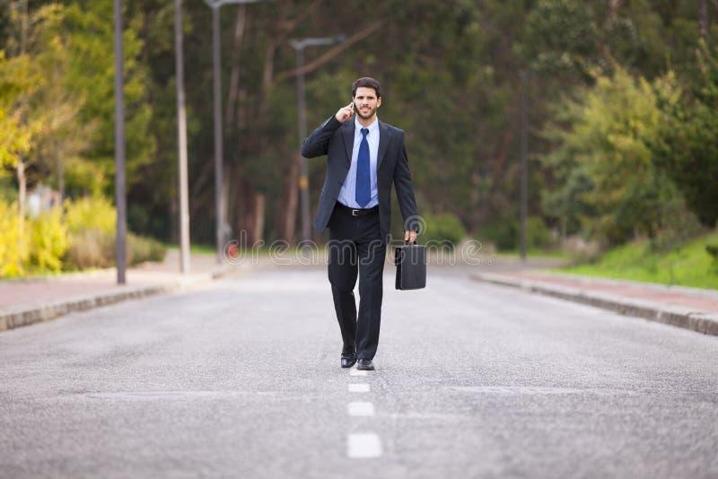Επιχειρηματίας που περπατά στην οδική γραμμή στοκ εικόνες
