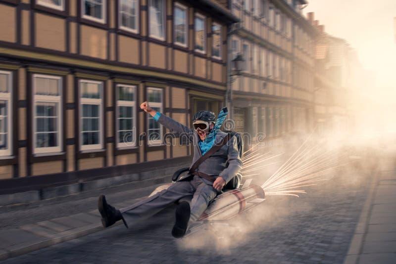 Επιχειρηματίας που πετά με την καρέκλα πυραύλων μέσω της πόλης στοκ φωτογραφίες με δικαίωμα ελεύθερης χρήσης