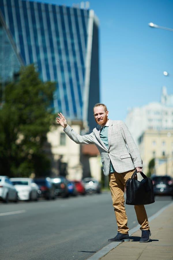 Επιχειρηματίας που πιάνει το ταξί στην οδό στοκ εικόνες
