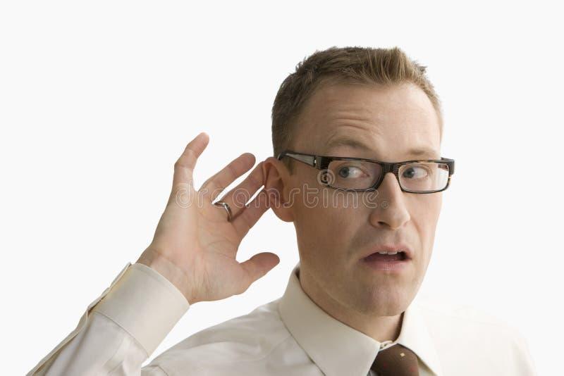 Επιχειρηματίας που προσπαθεί να ακούσει - απομονωμένος στοκ φωτογραφία