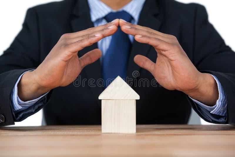 Επιχειρηματίας που προστατεύει το πρότυπο σπιτιών με τα χέρια στοκ εικόνες
