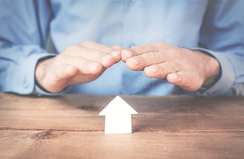 Επιχειρηματίας που προστατεύει το σπίτι εγγράφου Ασφαλιστική έννοια σπιτιών στοκ φωτογραφία με δικαίωμα ελεύθερης χρήσης