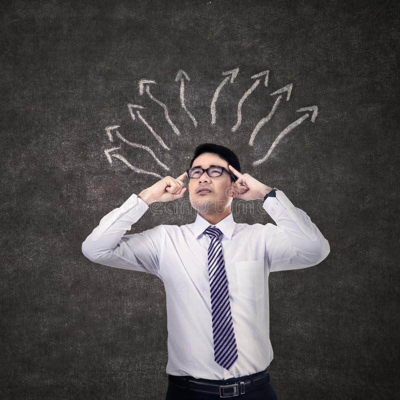 Επιχειρηματίας που σκέφτεται με το σημάδι βελών στοκ εικόνα