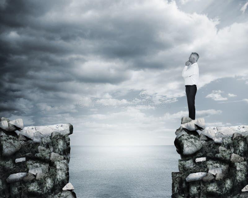 Επιχειρηματίας που σκέφτεται στην άκρη ενός απότομου βράχου στοκ εικόνες