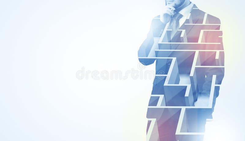 Επιχειρηματίας που στέκεται και που σκέφτεται με το λαβύρινθο στοκ φωτογραφία