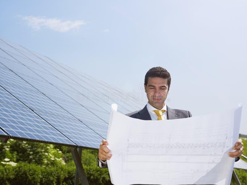Επιχειρηματίας που στέκεται κοντά στα ηλιακά πλαίσια στοκ εικόνες