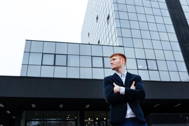 Επιχειρηματίας που στέκεται με τα όπλα που διπλώνονται υπαίθρια στοκ εικόνα