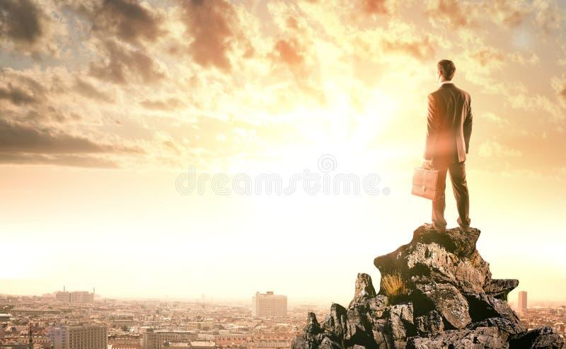 Επιχειρηματίας που στέκεται με την πλάτη ενάντια στην πόλη στοκ φωτογραφία με δικαίωμα ελεύθερης χρήσης