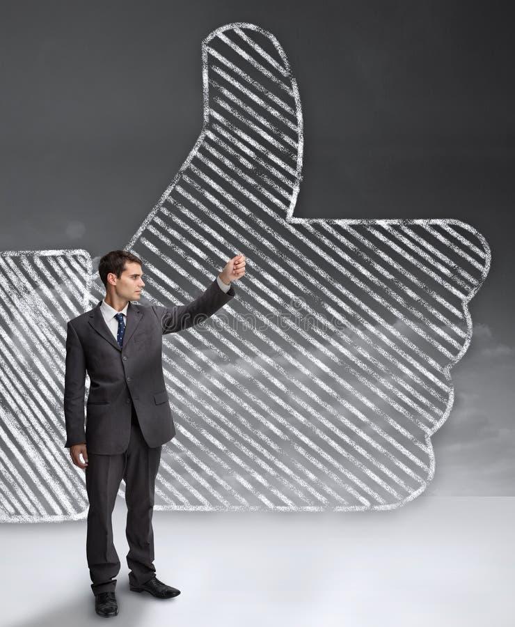 Επιχειρηματίας που στέκεται μπροστά από έναν γιγαντιαίο αντίχειρα επάνω στοκ εικόνες με δικαίωμα ελεύθερης χρήσης