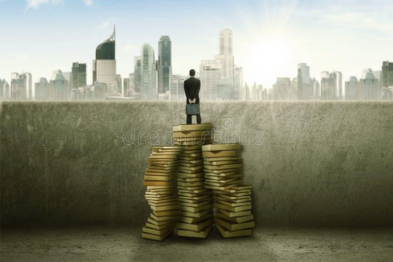 Επιχειρηματίας που στέκεται πάνω από το σωρό των βιβλίων που απασχολούν την πόλη στοκ φωτογραφίες