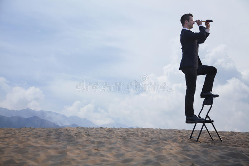 Επιχειρηματίας που στέκεται σε μια καρέκλα και που κοιτάζει μέσω ενός τηλεσκοπίου στη μέση της ερήμου στοκ εικόνες