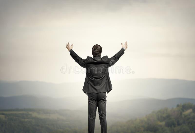 Επιχειρηματίας που στέκεται στην άκρη ενός απότομου βράχου μαύρη ελευθερία έννοιας που απομονώνεται στοκ εικόνα