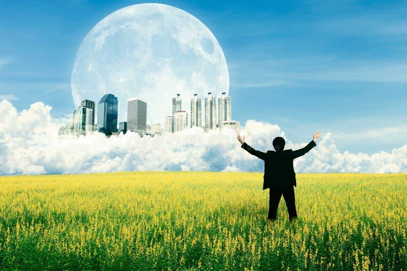 Επιχειρηματίας που στέκεται στον τομέα και που προσέχει τη μελλοντική πόλη στοκ φωτογραφίες