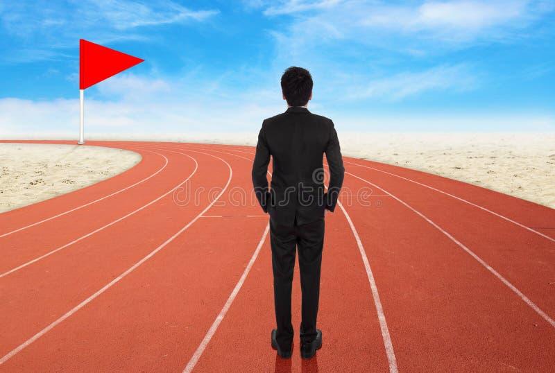 Επιχειρηματίας που στέκεται στο τρέξιμο της διαδρομής και το κοίταγμα στο στόχο στοκ εικόνες