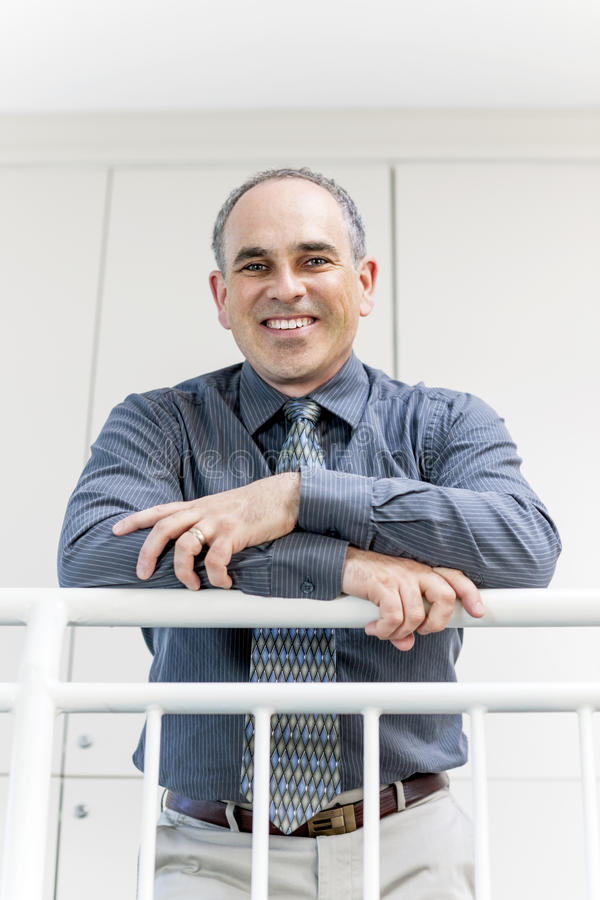Επιχειρηματίας που στέκεται στο χαμόγελο διαδρόμων γραφείων στοκ φωτογραφία με δικαίωμα ελεύθερης χρήσης