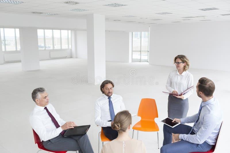 Επιχειρηματίας που συζητά με τους συναδέλφους στο νέο γραφείο στοκ εικόνες