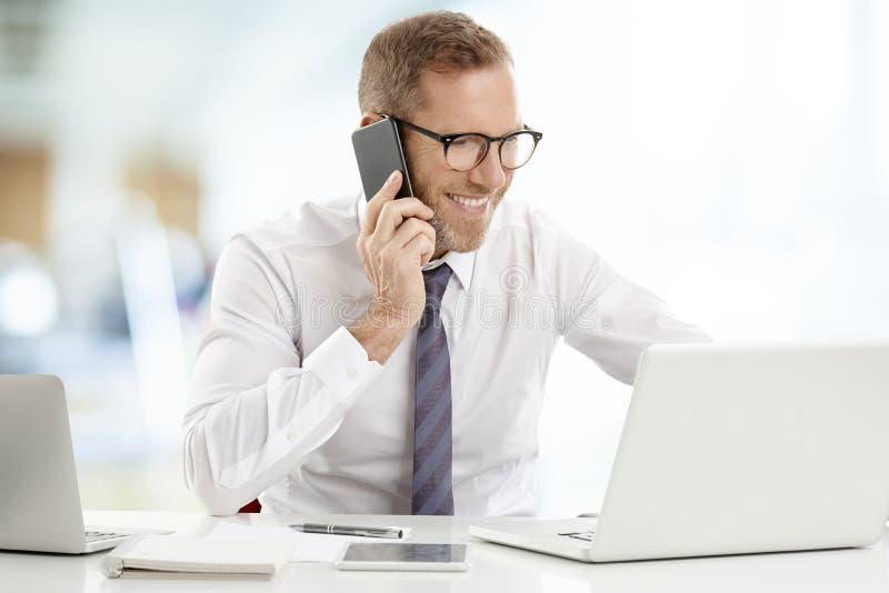 Επιχειρηματίας που συμβουλεύεται για το κινητό τηλέφωνο με τον πελάτη του στοκ εικόνες