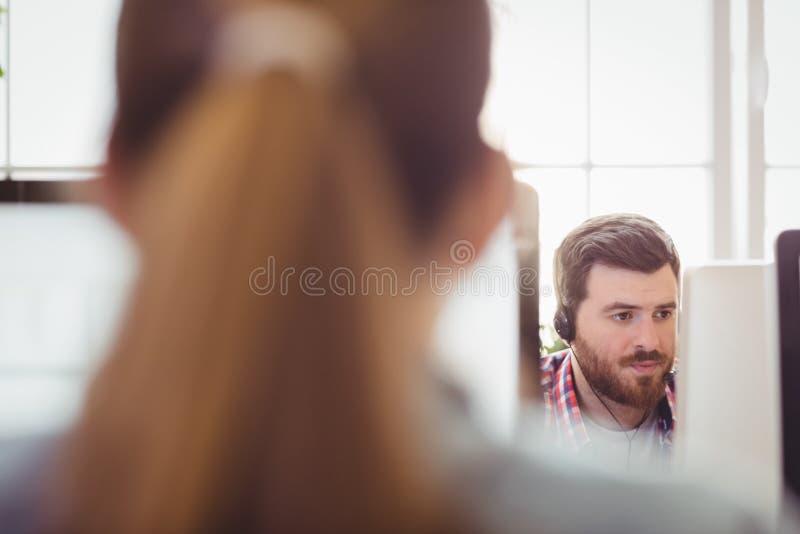 Επιχειρηματίας που συνεργάζεται με το συνάδελφο στον υπολογιστή στο δημιουργικό γραφείο στοκ φωτογραφία