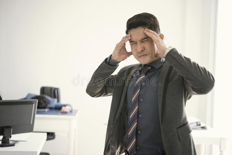 Επιχειρηματίας που τονίζεται και δυστυχισμένος για την εργασία στο γραφείο στοκ εικόνες