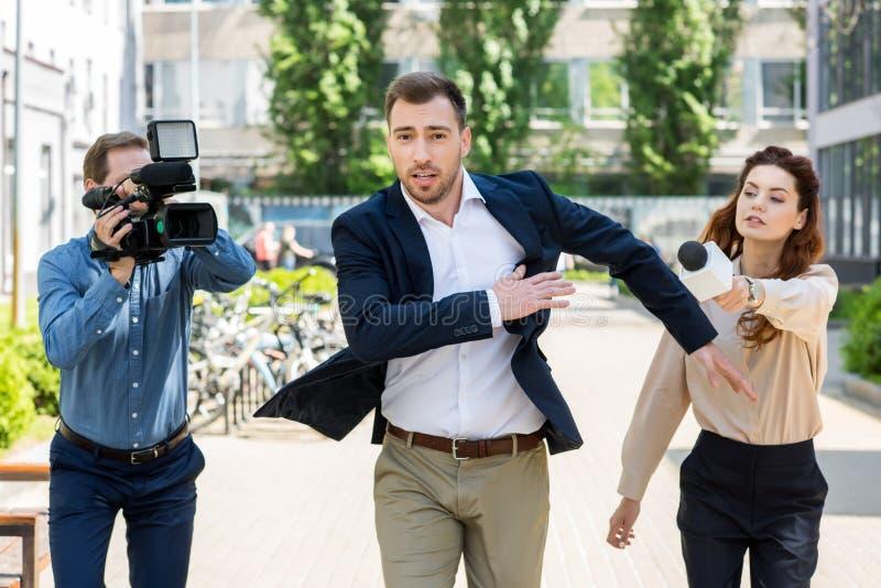 επιχειρηματίας που τρέχει από τους δημοσιογράφους με τα ψηφιακά βιντεοκάμερα στοκ εικόνες με δικαίωμα ελεύθερης χρήσης