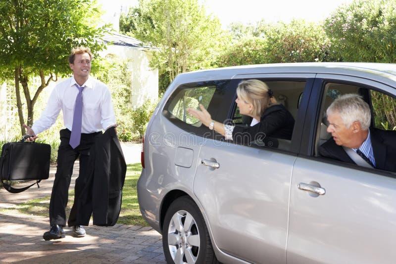 Επιχειρηματίας που τρέχει αργά για να συναντήσει το αυτοκίνητο συναδέλφων που συγκεντρώνει το ταξίδι στην εργασία στοκ εικόνες