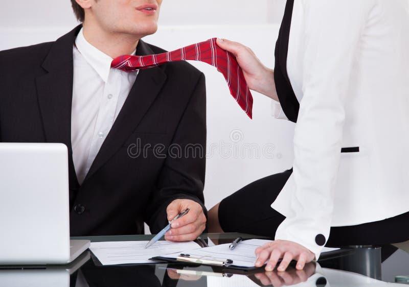 Επιχειρηματίας που τραβά το δεσμό του αρσενικού συναδέλφου παραπλανώντας τον στοκ φωτογραφία με δικαίωμα ελεύθερης χρήσης