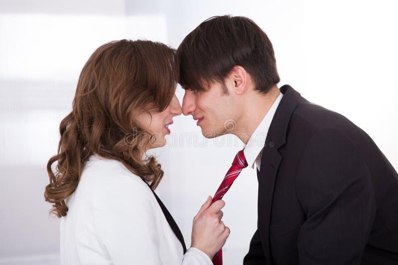 Επιχειρηματίας που τραβά το δεσμό του αρσενικού συναδέλφου παραπλανώντας τον στοκ φωτογραφίες με δικαίωμα ελεύθερης χρήσης