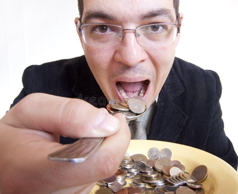 επιχειρηματίας που τρώει τα χρήματα στοκ εικόνες