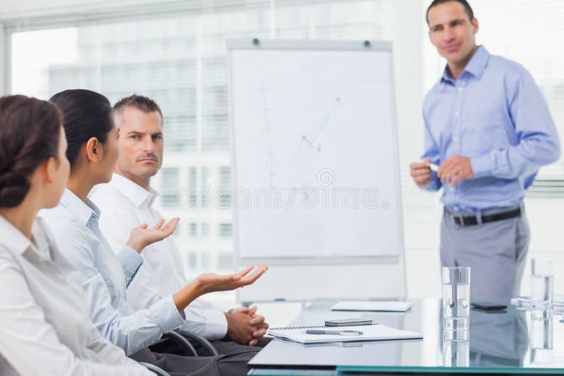 Επιχειρηματίας που υποβάλλει την ερώτηση κατά τη διάρκεια της παρουσίασης στοκ εικόνα με δικαίωμα ελεύθερης χρήσης
