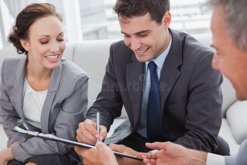 Επιχειρηματίας που υπογράφει τη σύμβαση ενώ ο συνεργάτης του εξετάζει τον στοκ φωτογραφία