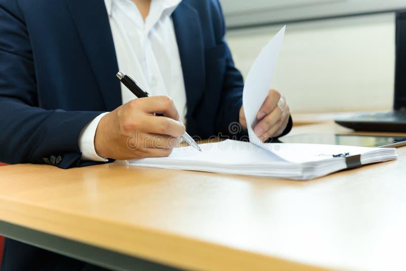 Επιχειρηματίας που υπογράφει το έγγραφο συμβάσεων με τη μάνδρα στο γραφείο γραφείων στοκ εικόνες
