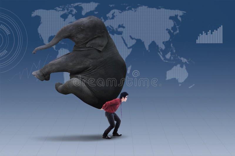 Επιχειρηματίας που φέρνει το βαρύ ελέφαντα πέρα από τον παγκόσμιο χάρτη στοκ φωτογραφία