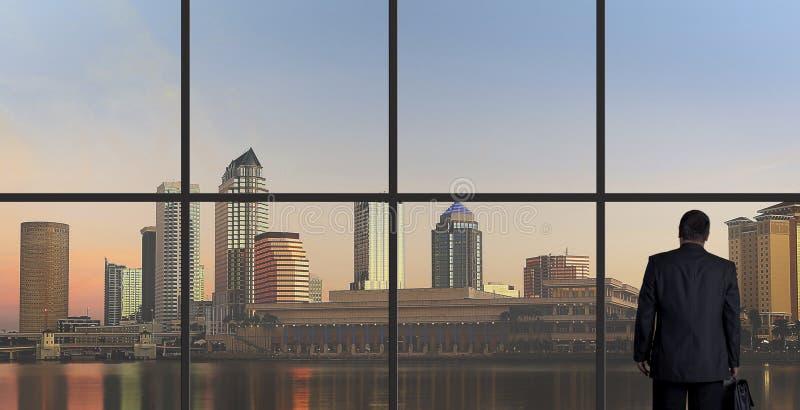 Επιχειρηματίας που φαίνεται έξω ένα παράθυρο γραφείων, τέλος της ημέρας στοκ εικόνες